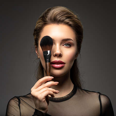 Portrait of a girl with cosmetic brush in hand. Woman covering one eye on the face using makeup brush. Woman makes makeup.