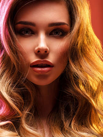 Portrait of beautiful young woman with bright shiny makeup. Blonde with brightly colored long hair. Pretty girl with long curly hair.   Fashion model posing at studio. Reklamní fotografie