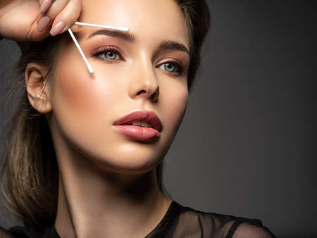 Beautiful face of a young woman with a cotton stick in her hand, isolated. Removing makeup with a cotton stick near eyes Reklamní fotografie