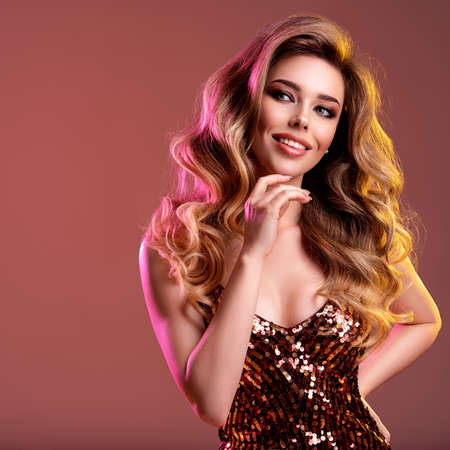 Portrait of happy beautiful young woman with bright shiny makeup. Smiling Blonde with brightly colored long hair. Pretty girl with long curly hair.  Fashion model in a shiny dress posing at studio.