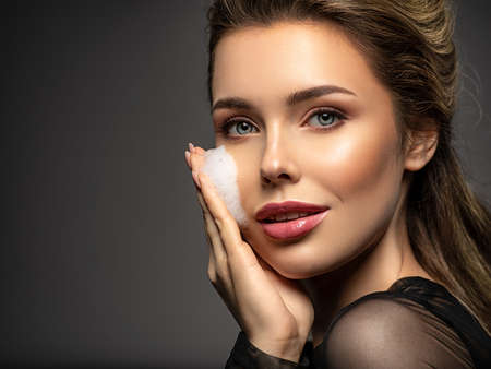 Woman with soap foam on face. Beautiful face of young caucasian woman with perfect healthy skin.  Pretty white model caring of face. Skin care concept.