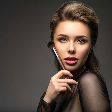 Portrait of a girl with cosmetic brush in hand. Woman makes makeup using cosmetics. Blonde model with a bright make-up.
