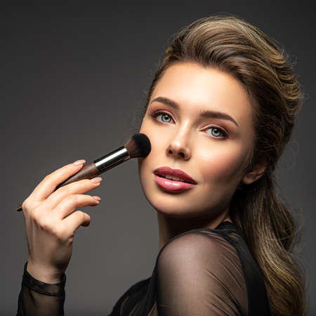 Portrait of a girl with cosmetic brush in hand. Woman makes makeup using cosmetics. Blonde model with a bright make-up. Reklamní fotografie