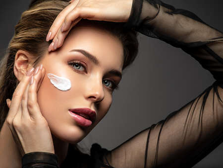 Woman face close-up with stripes of cosmetic cream on the face. The concept of makeup and cosmetics.