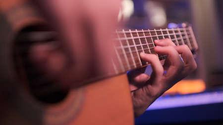 Close-up of a man's hands playing the guitar. The musician plays an acoustic guitar, closeup shot. Male fingers  plays on guitar. human hands plays on a guitar neck, soft focus