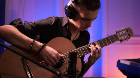 Musician in a headphones records his composition in a music Studio using professional audio microphone. Man plays guitar. Young man plays a musical instrument. Reklamní fotografie