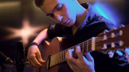 Man plays guitar. Young man plays a musical instrument. Musician records his composition in a music Studio using professional microphone