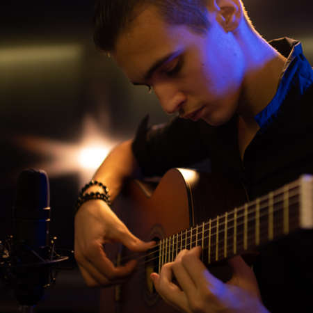 Man with a classical guitar in a neon glow. Teenager plays guitar.  Young man plays a musical instrument.
