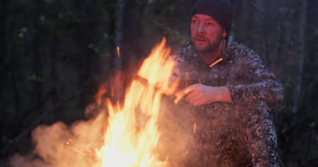 Adult man outdoors is cooking meal on fire. Man roasts sausages on a fire on nature. Person cooks dinner over a fire in the woods. Reklamní fotografie