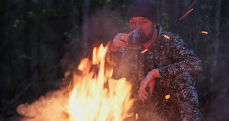 Man with cup of tea the fire in the forest. Human looks at the bonfire and drinks tea on the nature in the summer. Alone traveler sits and rests by the fire with a cup of coffee at dusk.