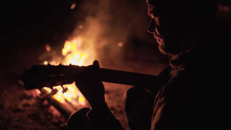 Man is playing guitar by the campfire in nature. Weekend in nature by the fire. Adult man is resting in forest near fire at night.