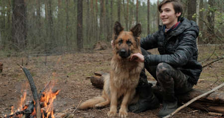 Young man with big dog sits at the fire in the forest. Cheerful guy is stroking his dog, outdoor. Happy caucasian teenager with his German shepherd by the fire in nature, in autumn.
