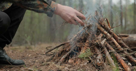Low angle shot of a man is trying make a fire in the forest. Close-up of a man's hand lighting a campfire. Lighting a fire in the forest by a person. Low angle of a burning fire made of brushwood. Reklamní fotografie