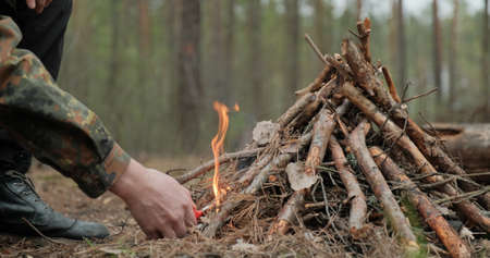 Man starts a fire in the forest using a lighter. Close-up of a man's hand lighting a fire with a lighter. Lighting a fire in the forest by a person. Low angle of a burning fire made of brushwood. Reklamní fotografie