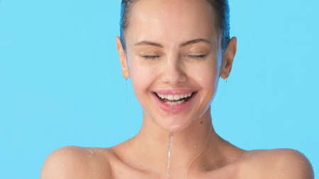 Female face with water on it. Young cheerful girl with water running down her face. Woman washing her clean face with water.