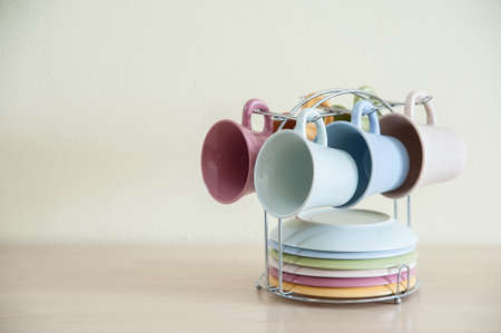 bar ware: Pile of colorful cups of coffee on wooden table with cream background. Left space of frame, wallpaper.