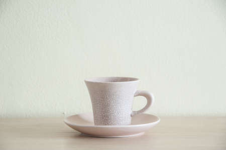 take a break: A cream coffee cup for take a break on the wooden table. Left space of frame.