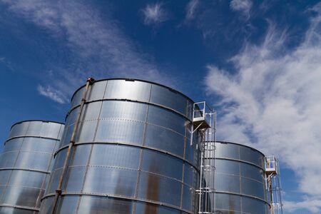 Tanques de almacenamiento de acero en un sitio industrial en Amsterdam, frente a un cielo azul con nubes blancas, Países Bajos.