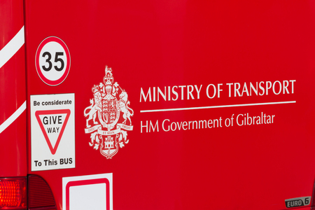 GIBRALTAR, UNITED KINGDOM - FEBRUARY 9, 2018: Public transport iconic red bus. Rear end decorated with the coat of arms from the Government of Gibraltar.