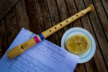 flute on a sheet music and half a lemon on a plate 写真素材