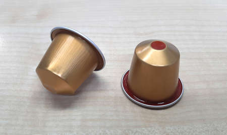 two golden coffee capsules one of them with a signal to contain decaffeinated coffee