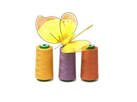 Coloreds spools with butterfly  isolated on white background photo