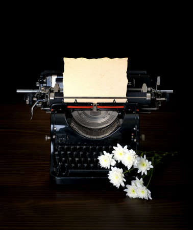 antique typing machine with paper for text  and flowers photo