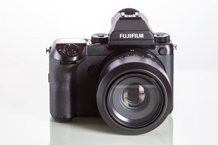 Fujifilm GFX 50S, 51 megapixels, medium format sensor digital camera with 63 mm G-mount lens on white reflecting background Editorial