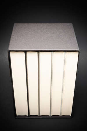 A set of five monochromatic cloth-bound books stored inside a black hard cardboard slipcase set on a slightly graduated and subtly textured dark background.
