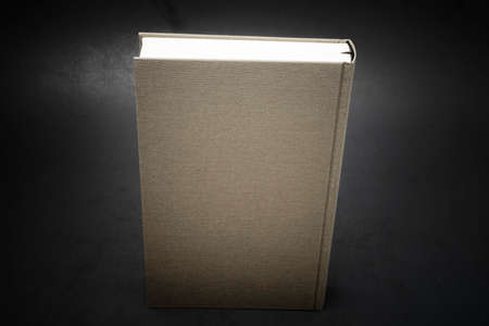 A close-up view of the top portion of a cloth-bound book with permanent black silk bookmark set on a dark background.