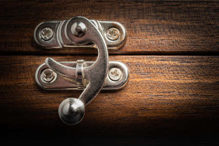 A close-up or macro look of a silver-color metal sliding lock latch installed on a polished wooden box in horizontal image format.