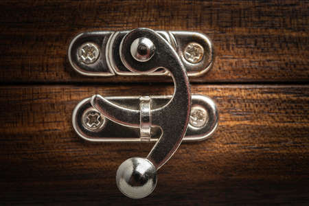 A close-up look of the fancy silver-color metal sliding latch on a wooden box. Imagens - 125394331