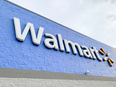 Vidalia, Georgia, USA - June 13, 2019 - The prominent lighted 3D brand and logo of Walmart on the top portion of its big box store facade in Vidalia, Georgia, USA.