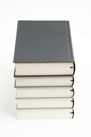 A set of five neatly stacked and arranged monochromatic cloth bound books on a plain white background.