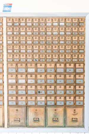 Rows of mid-century modern design post office mailboxes in brass metal.