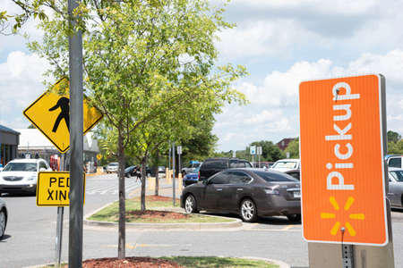 Vidalia, Georgia  USA - May 28, 2019: The reserved spots for Walmarts new Pickup service are marked with prominent orange signs.