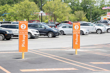 Vidalia, Georgia / USA - May 28, 2019: The reserved spots for Walmart's new Pickup service are marked with prominent orange signs.
