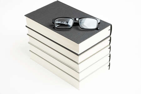 A neatly stacked set of five monochromatic cloth-bound books with reading eyeglasses on a plain white background. Imagens
