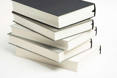 A disarrayed stack of five monochromatic cloth bound books set on a plain white background.