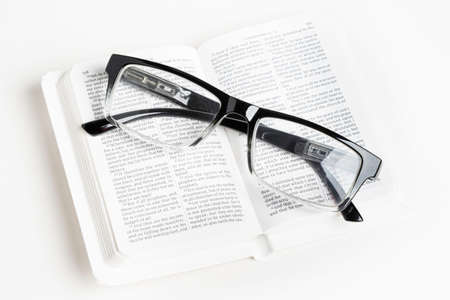 An open white portable pocket bible with a pair of clear reading glasses set on plain white background. Banco de Imagens