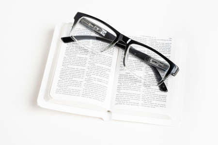 An open white portable pocket bible with a pair of clear reading glasses set on plain white background. Stock fotó