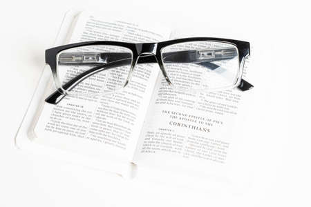 An open white portable pocket bible with a pair of clear reading glasses set on plain white background. 免版税图像