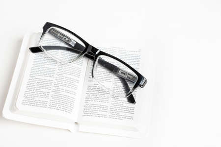 An open white portable pocket bible with a pair of clear reading glasses set on plain white background.