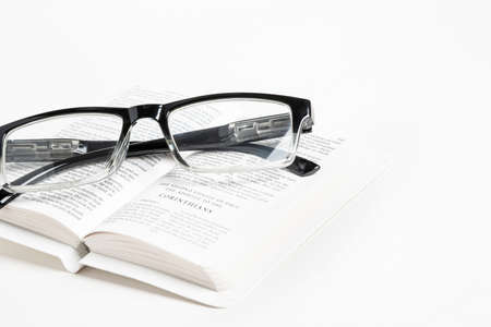 An open white portable pocket bible with a pair of clear reading glasses set on plain white background. 写真素材