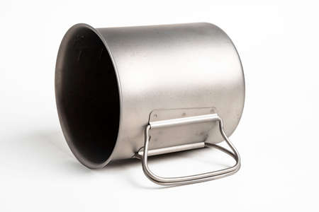 An all-metal multiple purpose mug with flexible handle and measuring mark set on a plain white background. Фото со стока