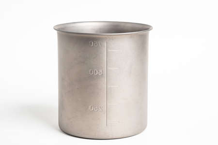 An all-metal multiple purpose mug with flexible handle and measuring mark set on a plain white background. Reklamní fotografie