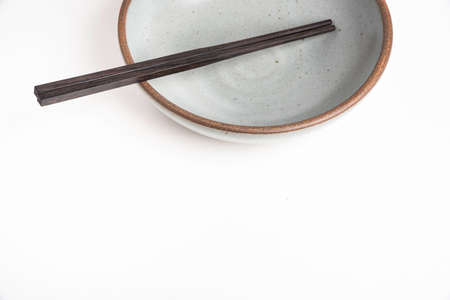 A pair of traditional wooden chopsticks with an empty earthenware bowl. 版權商用圖片