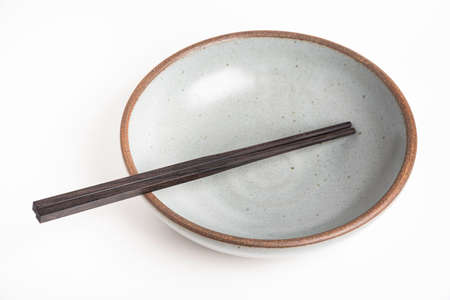 A pair of traditional wooden chopsticks with an empty earthenware bowl.