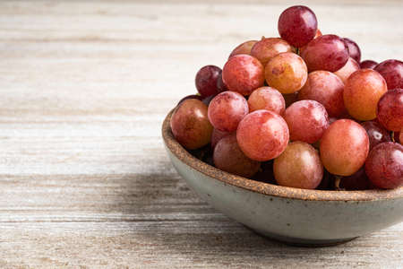 A bunch of fresh red grapes in an earthenware bowl set on a textured wood table.