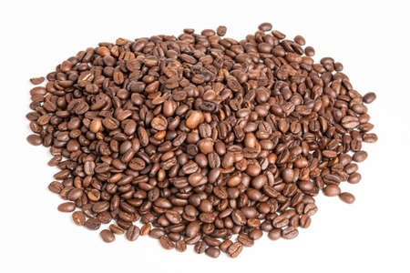 A mound of roasted coffee beans set on a plain white background.